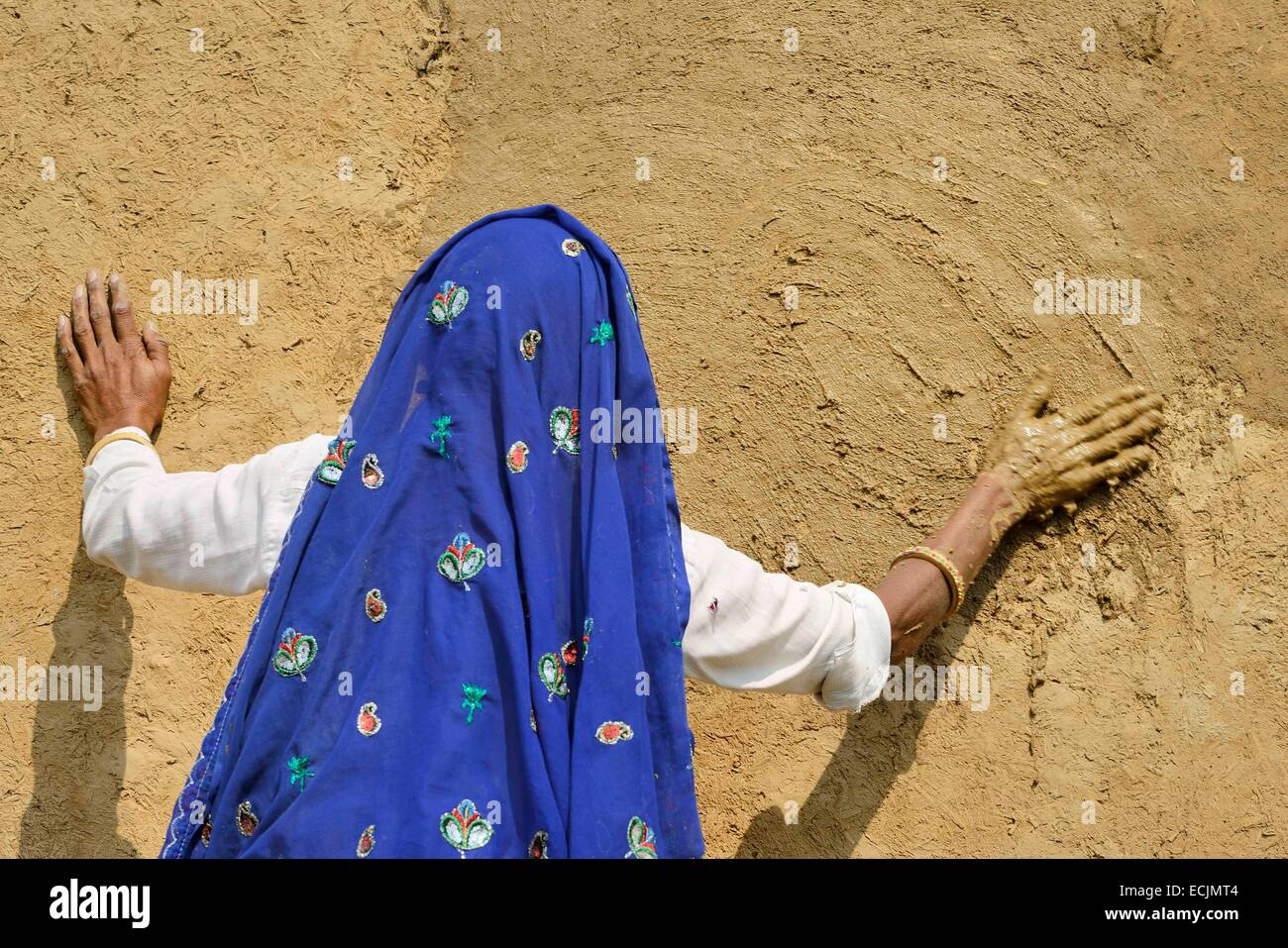 India, Rajasthan, Tonk region, Woman refurbishing her home walls with a coat of fresh clay prior to Diwali festival. - Stock Image