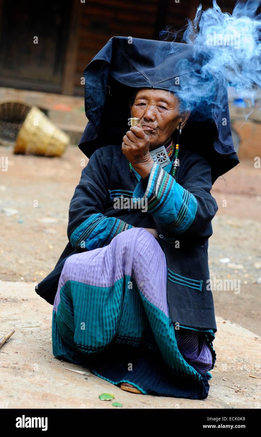 China, Yunnan Province, Yi minority woman smoking a pipe - Stock Image