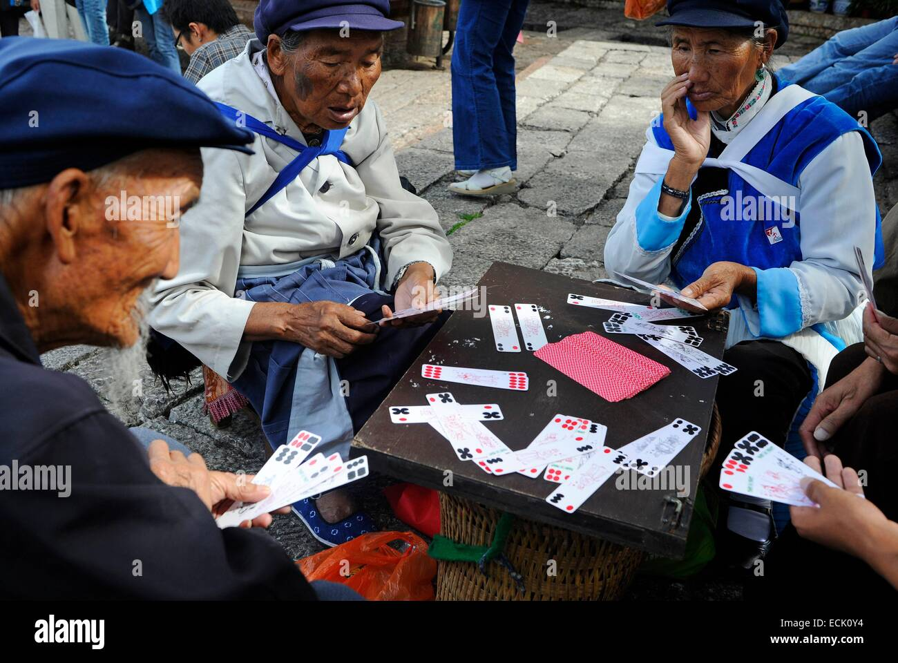China, Yunnan Province, Lijiang, Naxi women playing cards - Stock Image