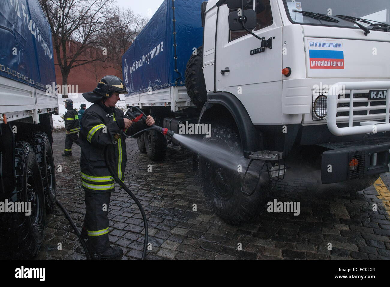 Moscow, Russia. 16th Dec, 2014. Russia's emergency situations ministry officer washes a truck ahead of a KAMAZ - Stock Image