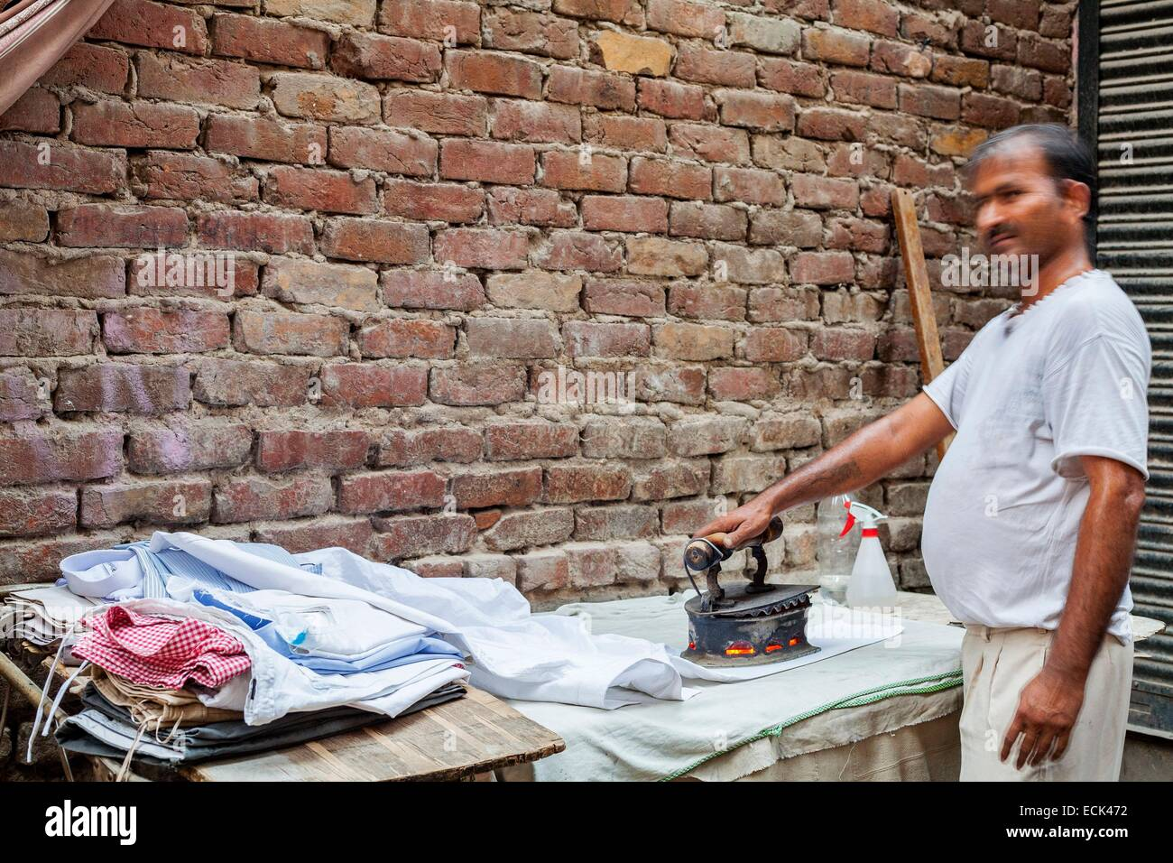 India, New Delhi, Khirkeel district, Bleacher still using an iron to embers - Stock Image