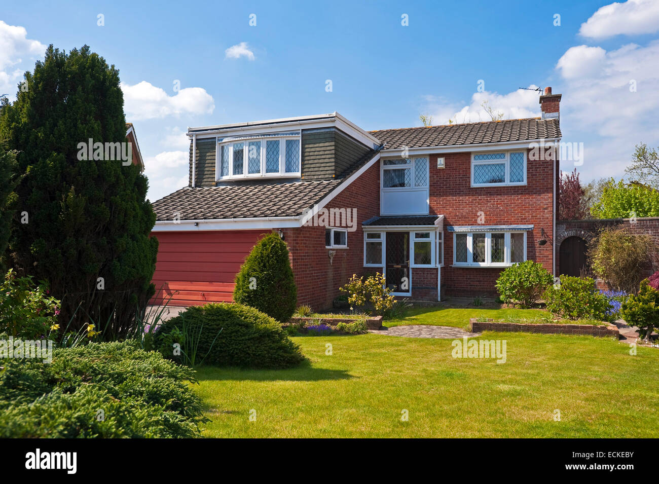 Horizontal exterior of a typical 1980's detached house in the sunshine. Stock Photo