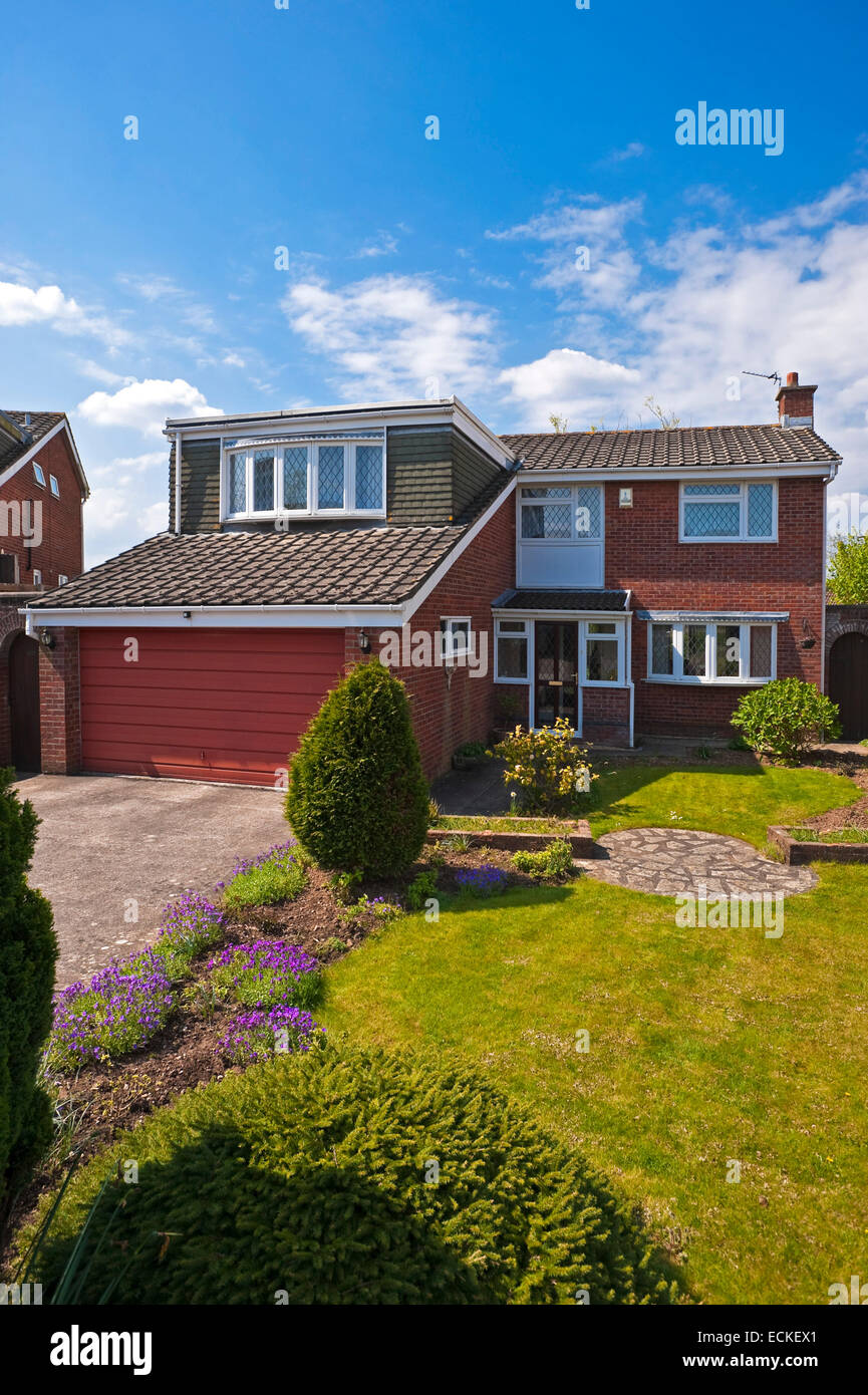 Vertical exterior of a typical 1980's detached house in the sunshine. Stock Photo