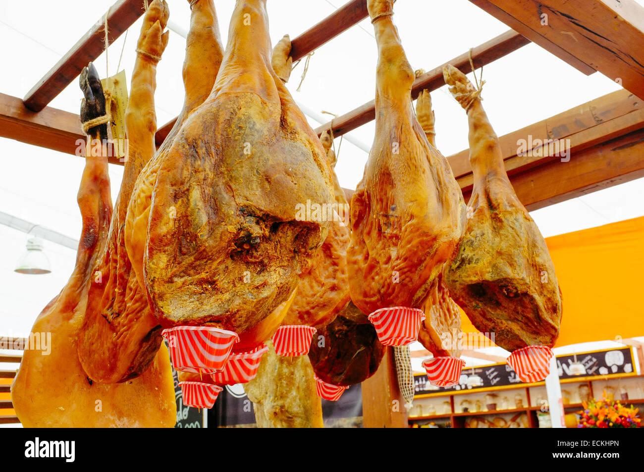 Iberian ham legs hanging on butcher - Stock Image