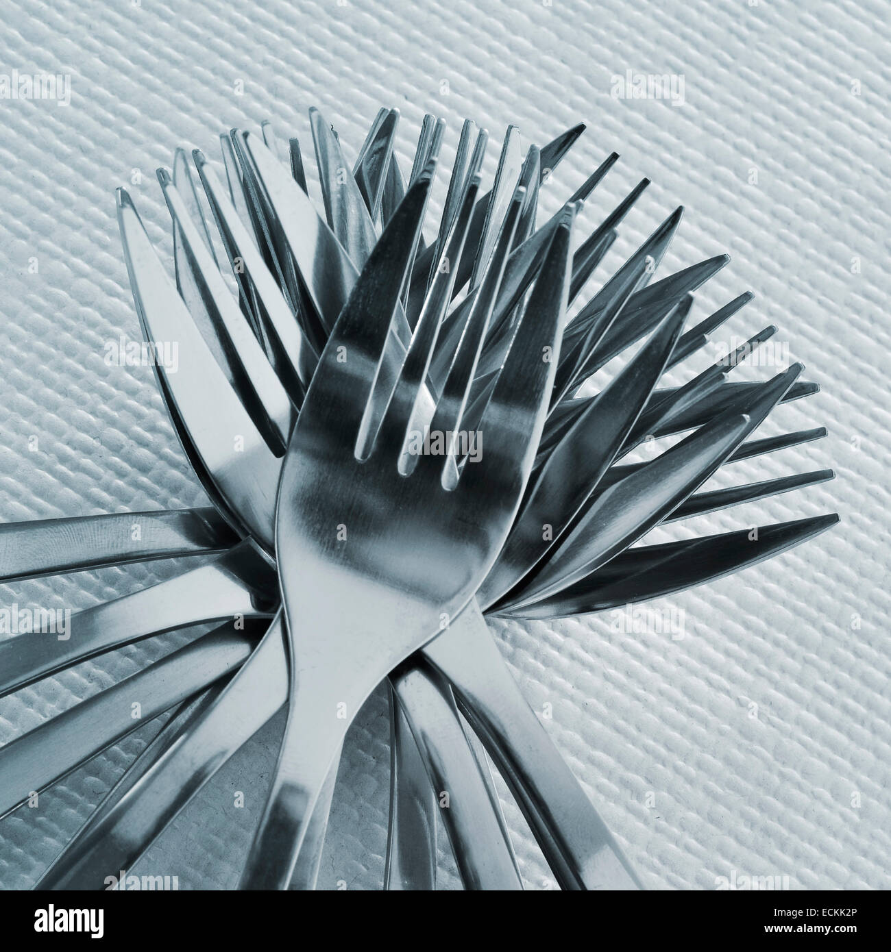 closeup of a pile of forks on a set table with a textured tablecloth - Stock Image