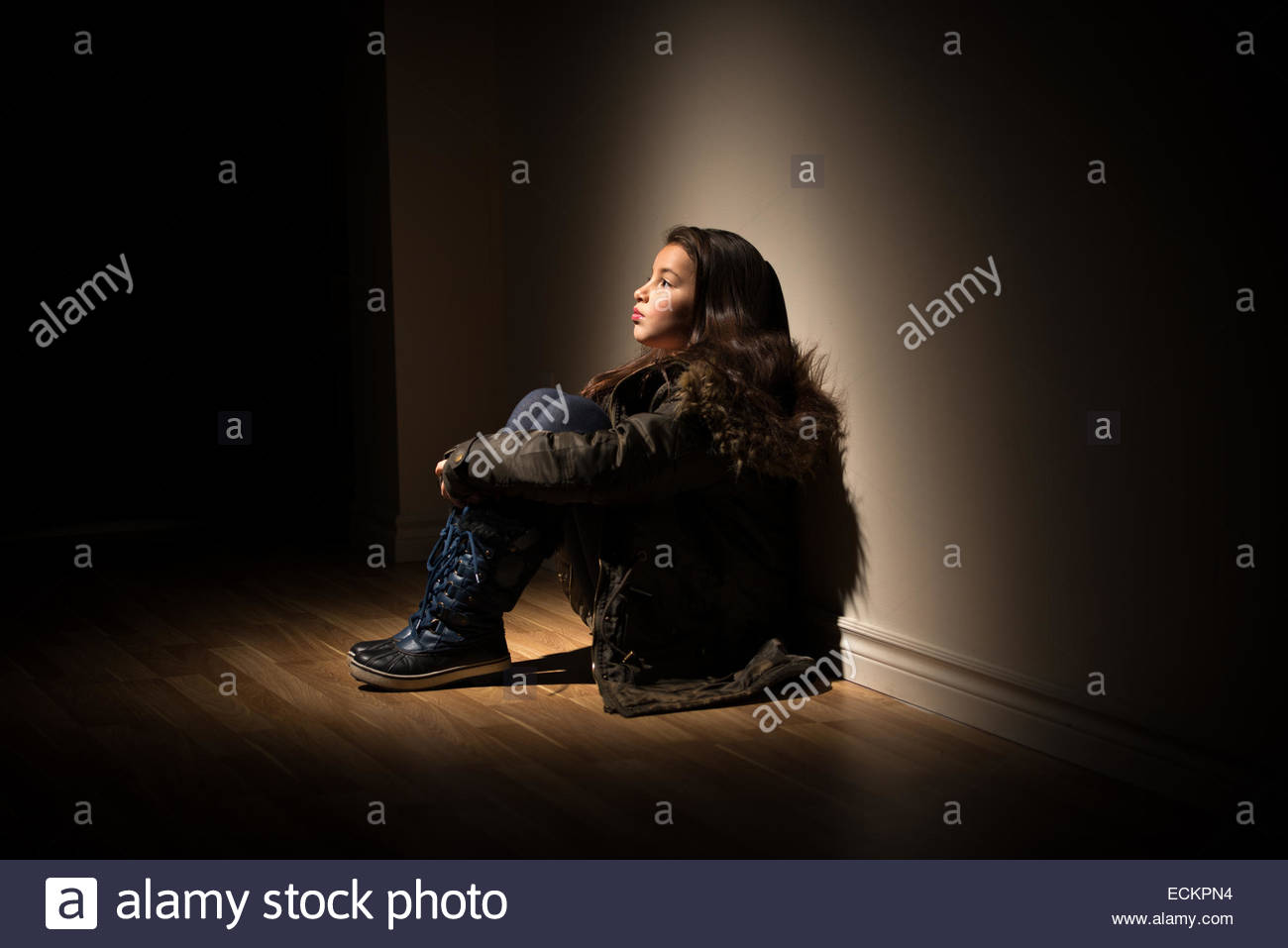 Young girl sitting under a spotlight in a dark room in a coat ...
