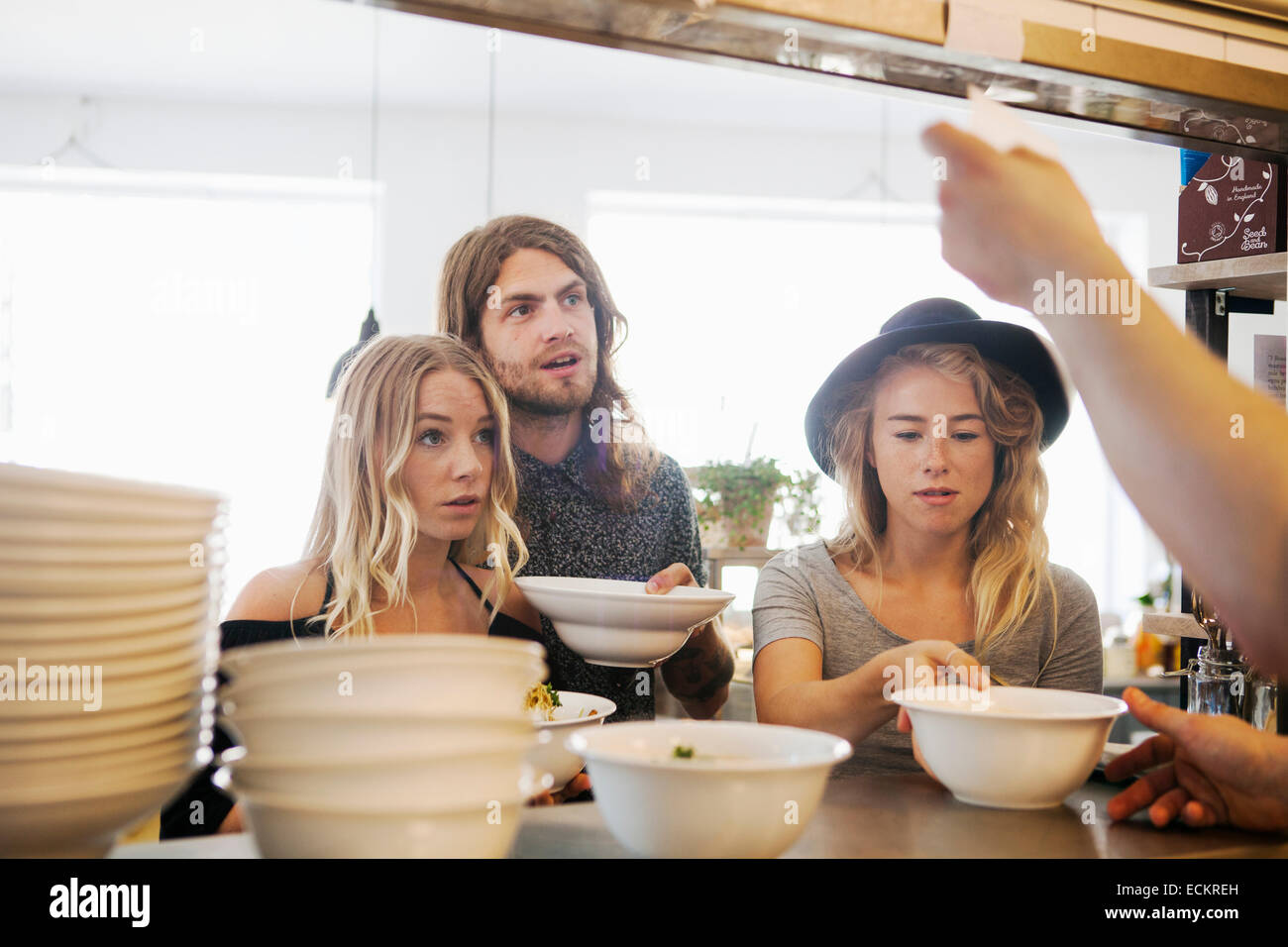 Friends taking food from counter at restaurant - Stock Image