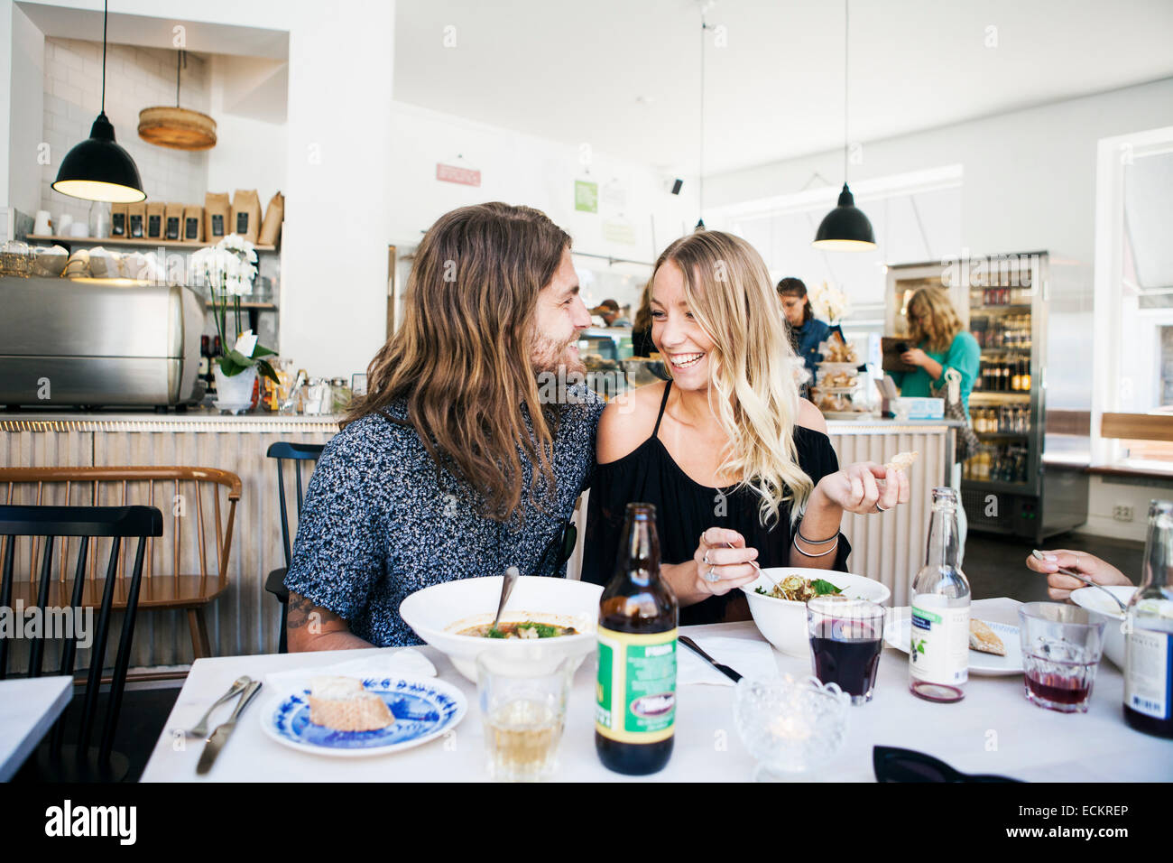 Happy couple talking while having food at restaurant table - Stock Image