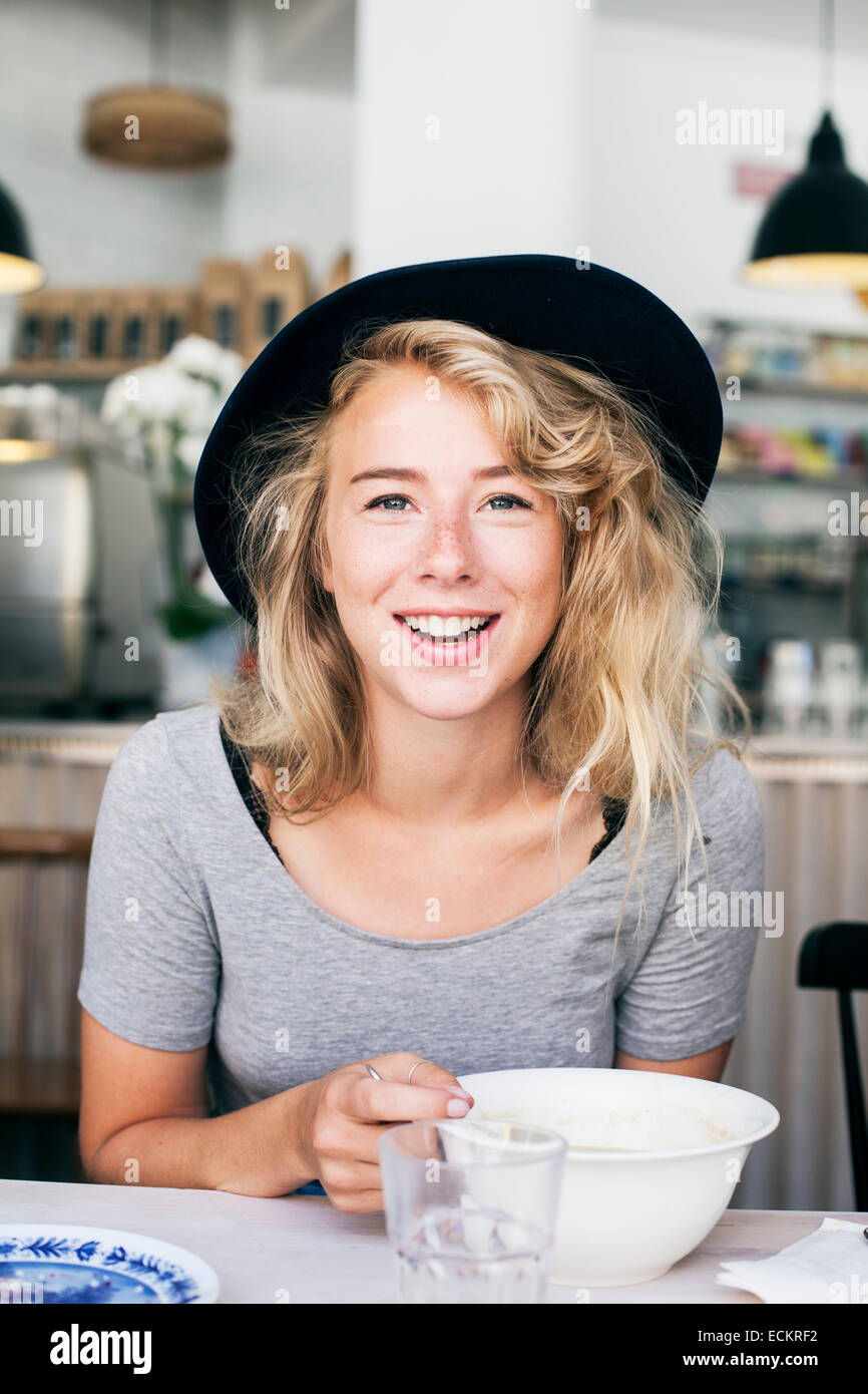 Portrait of happy young woman in restaurant - Stock Image