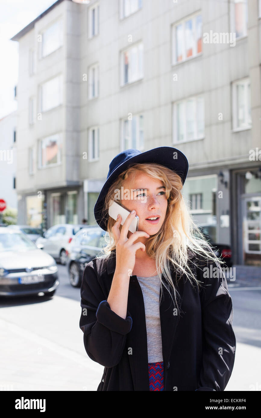 Young woman using smart phone on city street - Stock Image