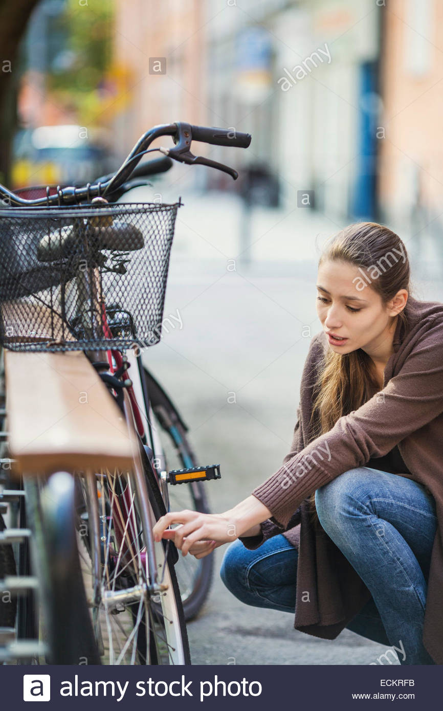 Young woman crouching while repairing bicycle Stock Photo