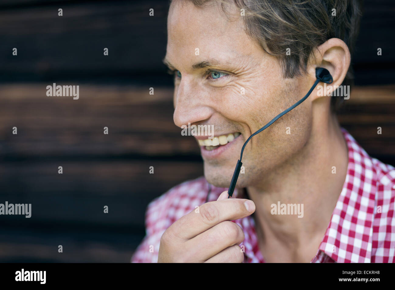 Happy man using hands-free device outside log cabin - Stock Image