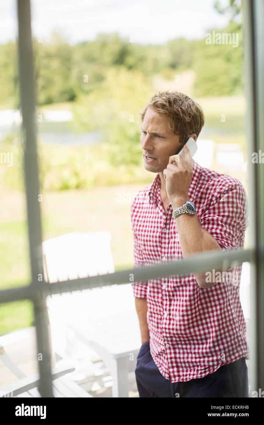 Man using mobile phone at porch - Stock Image