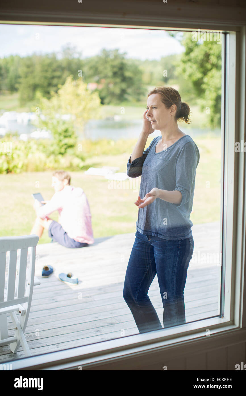 Couple using technologies on porch - Stock Image