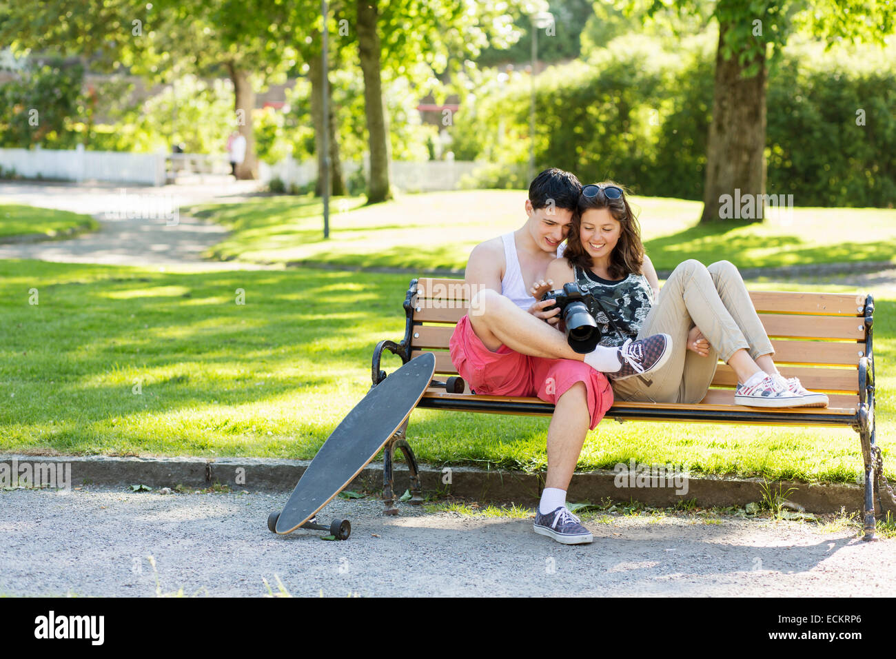 Happy loving couple looking photos on camera while sitting on bench in park - Stock Image