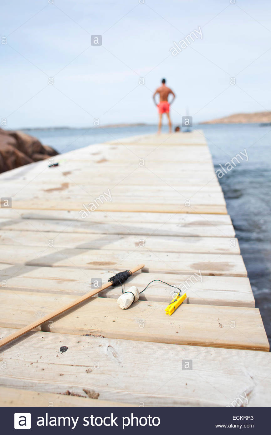 Fishing rod on wooden pier at lake with man standing in background against sky - Stock Image