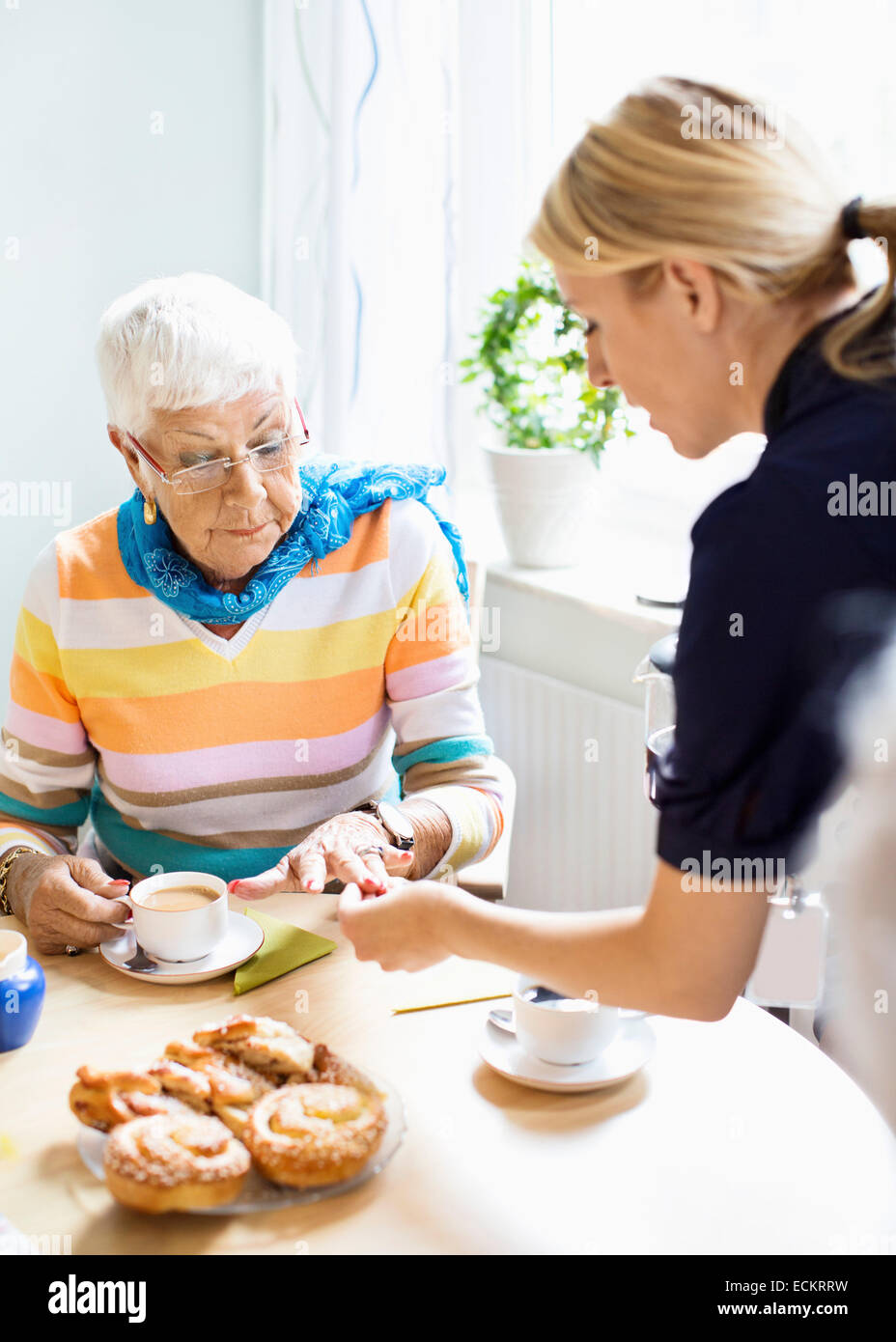 Female caretaker examining senior woman's finger at breakfast table in nursing home - Stock Image