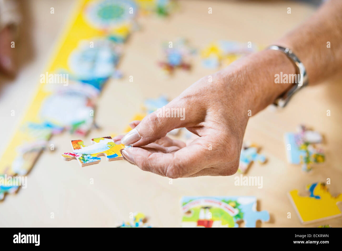Cropped image of senior woman's hand holding jigsaw piece at table in nursing home - Stock Image