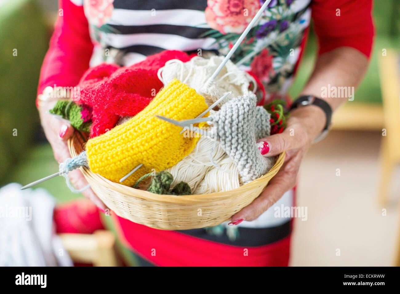 Midsection of senior woman holding knitting basket at nursing home - Stock Image