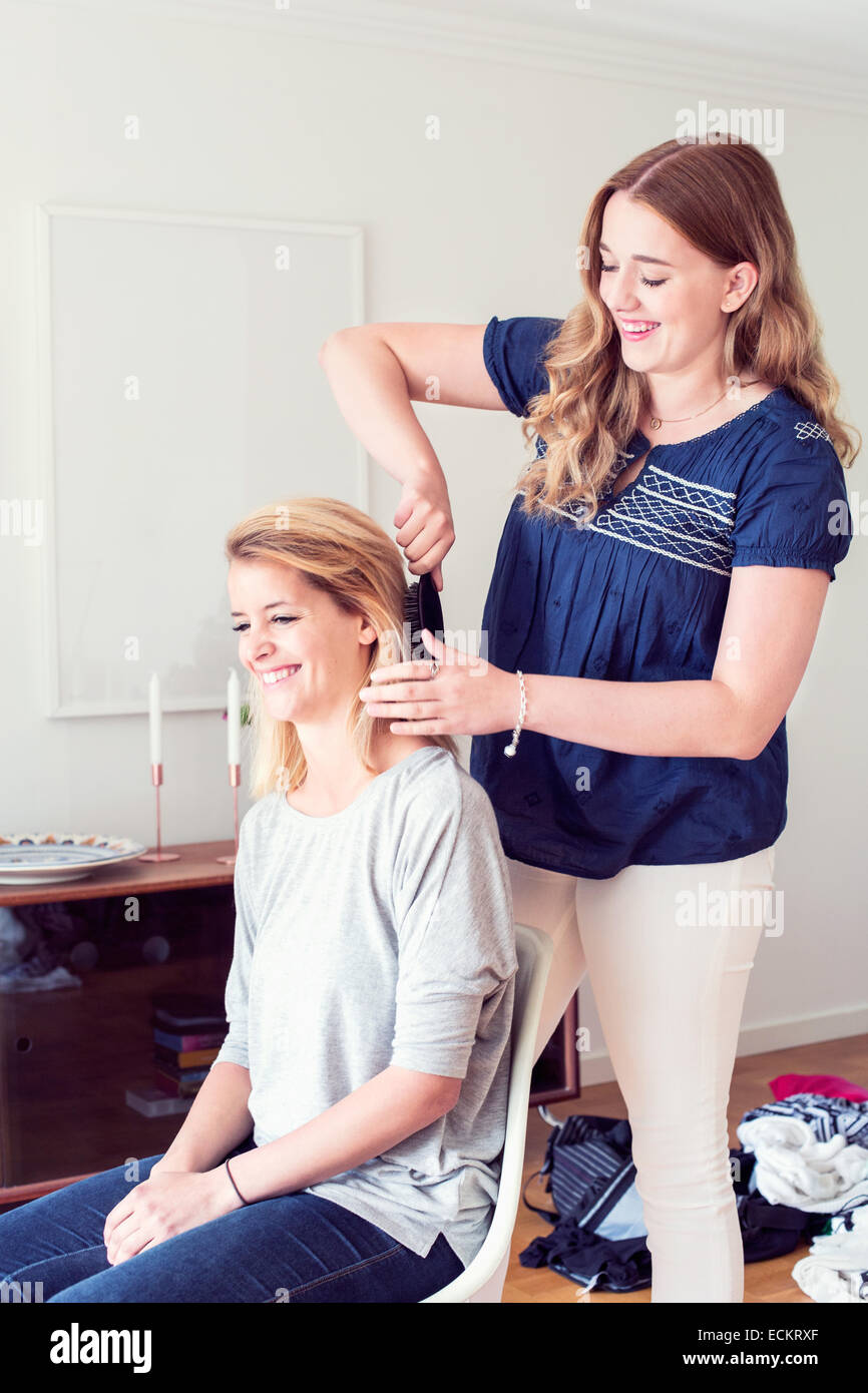 Young woman brushing sister's hair at home Stock Photo