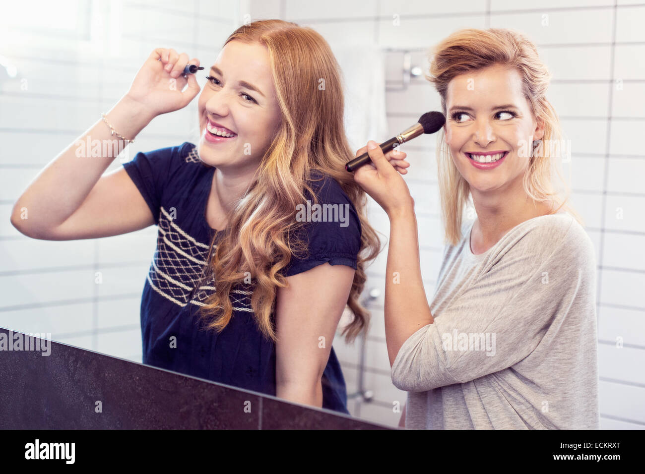 Happy young sisters applying makeup in mirror - Stock Image