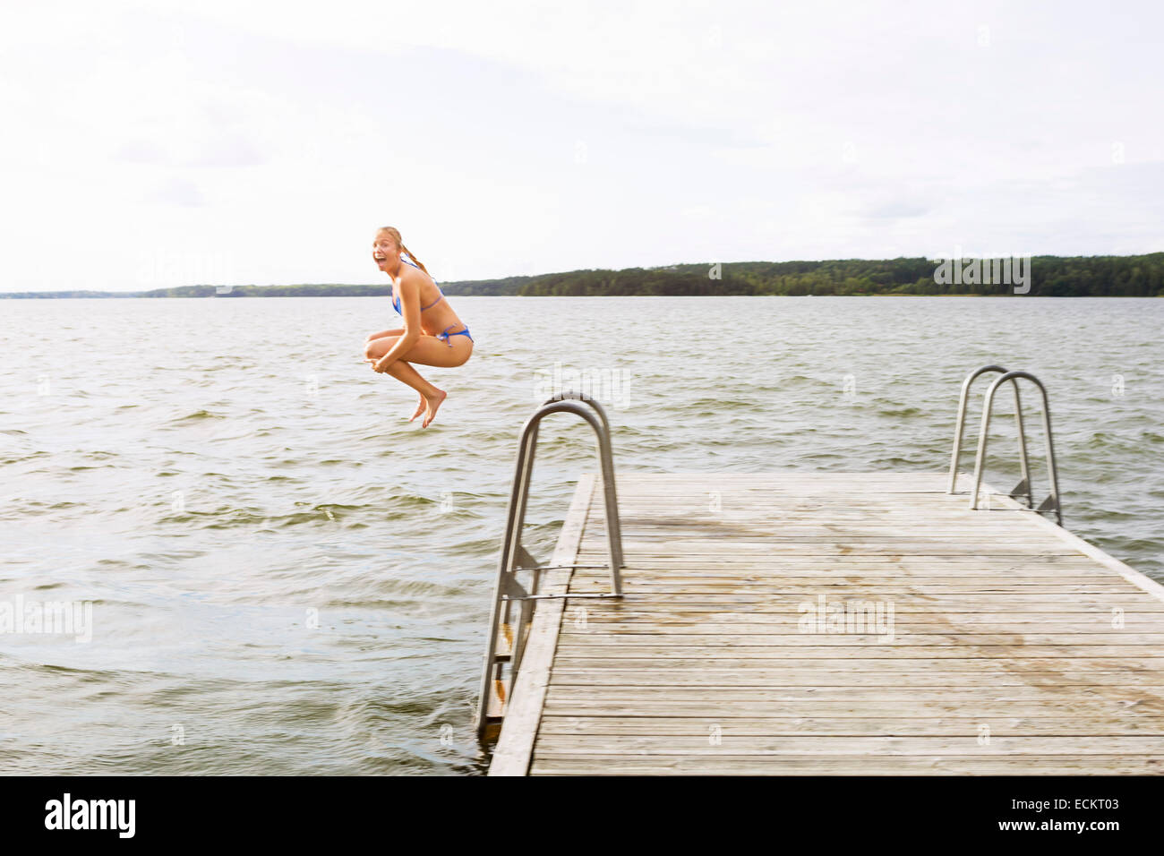 Full length side view of excited woman jumping into lake - Stock Image