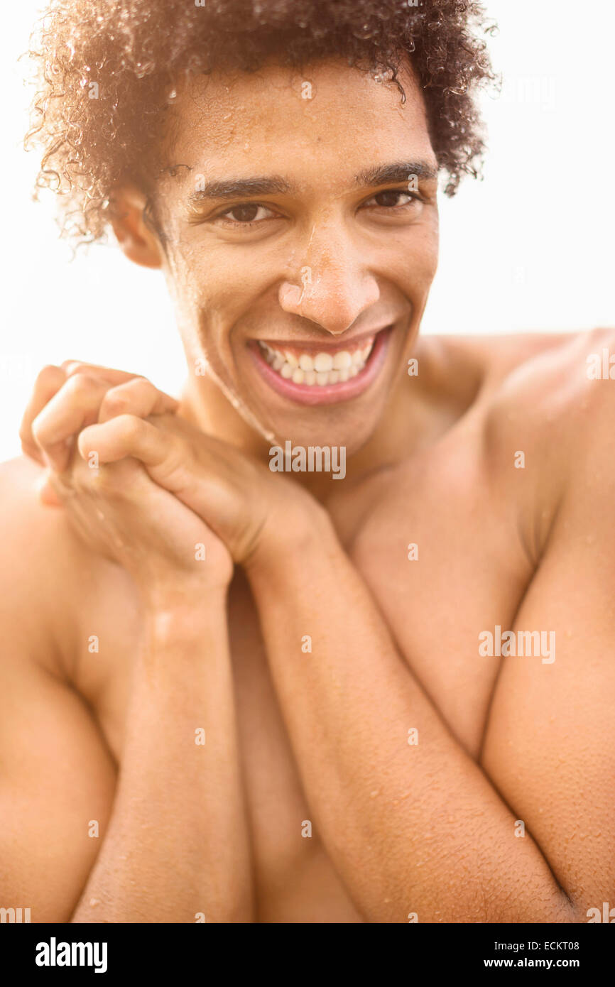 Portrait of happy wet shirtless man with hands clasped outdoors - Stock Image