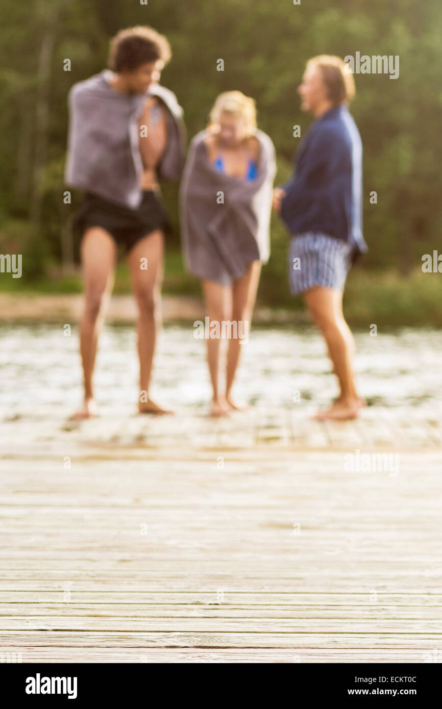Friends wrapped in towels standing at the edge of boardwalk - Stock Image
