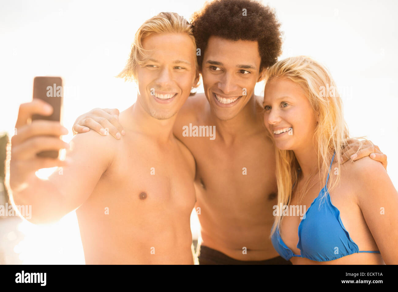 Friends taking self portrait on sunny day - Stock Image