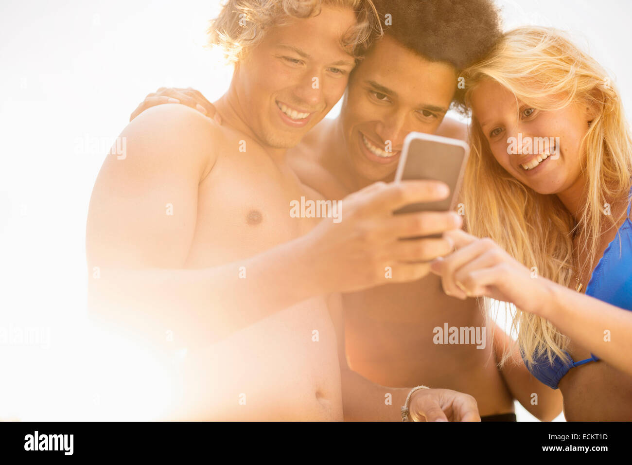 Happy friends using smart phone against sky on sunny day - Stock Image