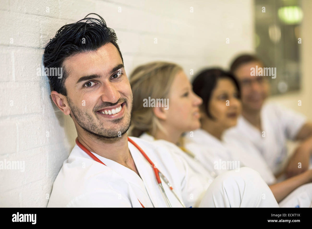 Portrait of smiling male doctor with female colleagues in hospital - Stock Image
