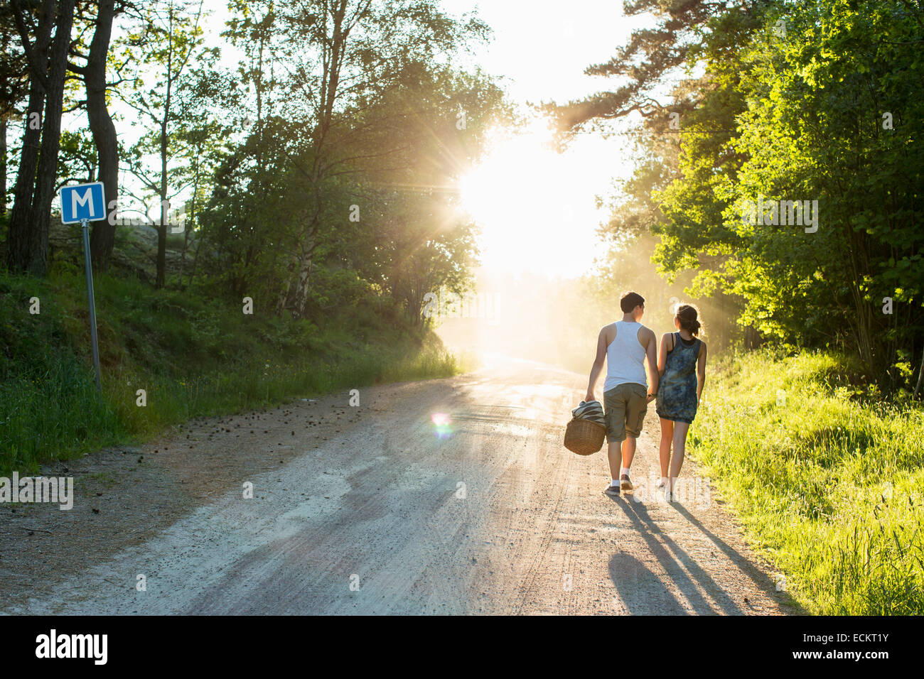 Full length rear view of couple walking on dirt road Stock Photo