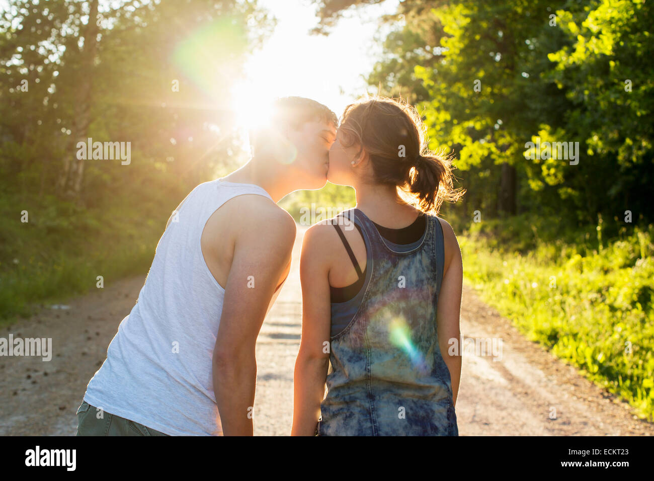 Rear view of couple kissing on dirt road against bright sun - Stock Image