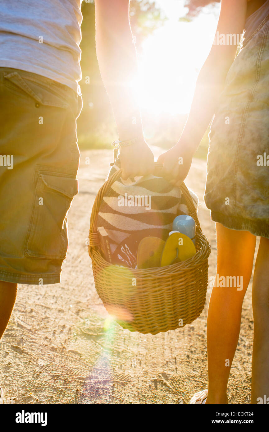 Midsection of couple carrying picnic basket against bright sun - Stock Image