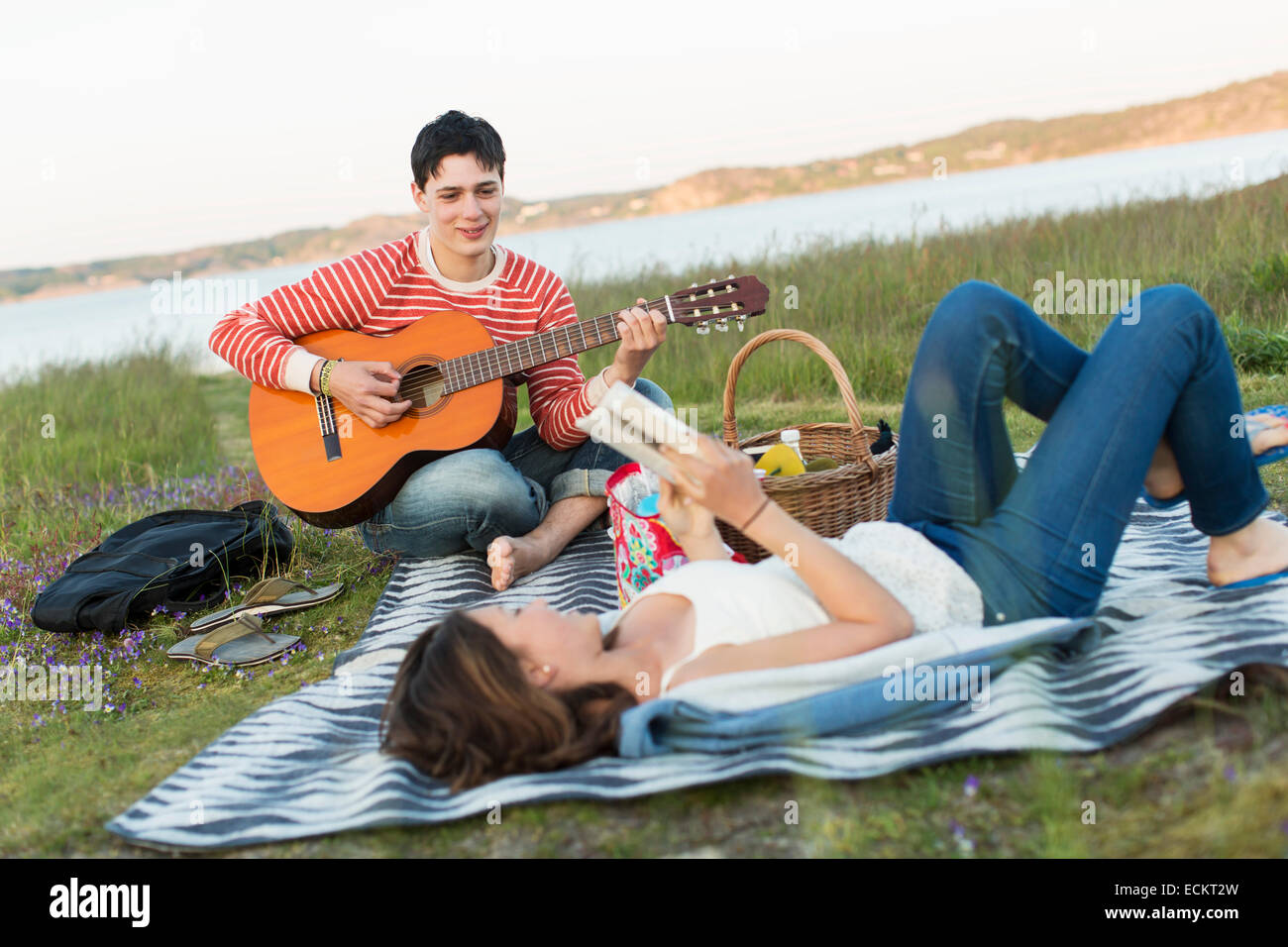Teenage girl reading book with boyfriend playing guitar during picnic Stock Photo
