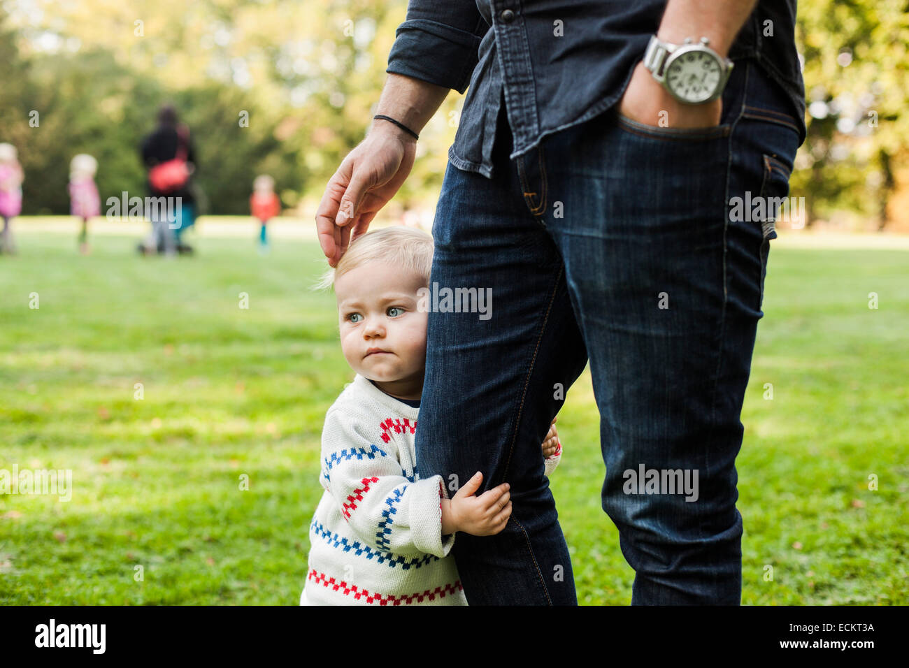 Baby girl holding father's leg in park - Stock Image