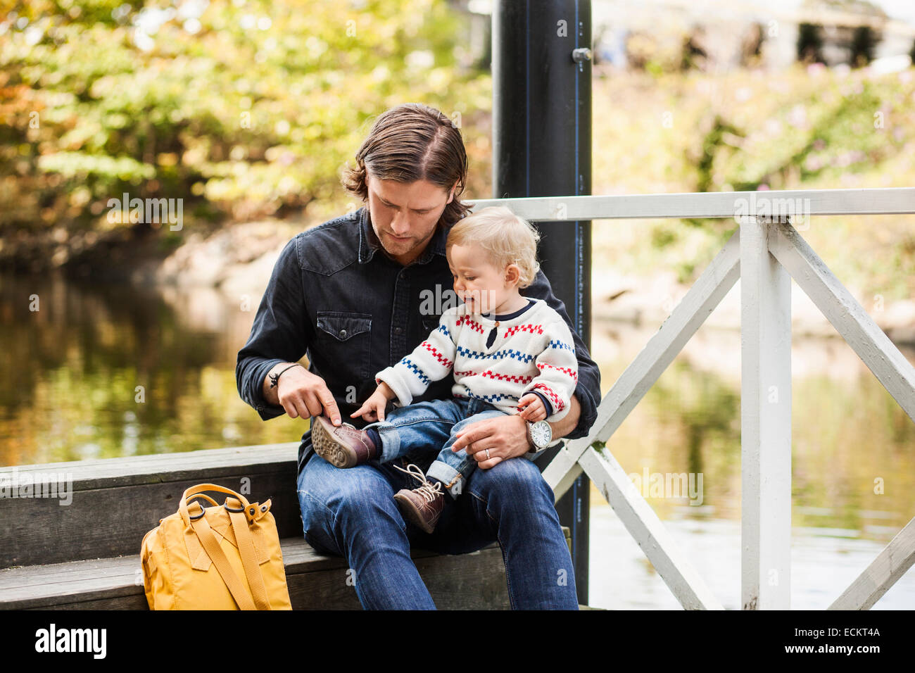 Baby girl showing shoe to father while sitting on steps at lakeshore - Stock Image