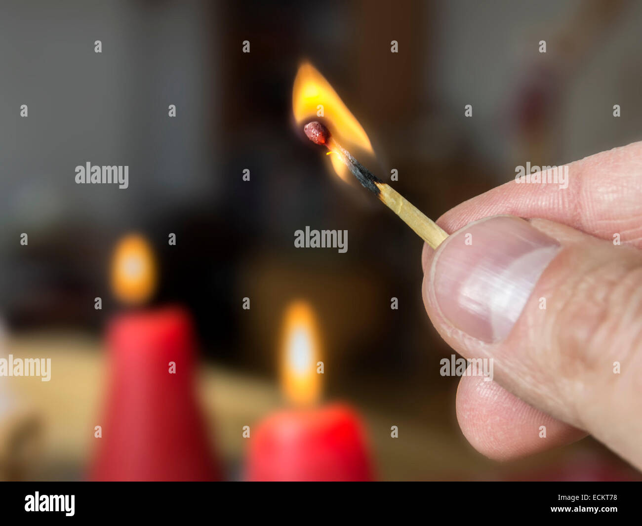 Picture of an burning match with candles in the background - Stock Image