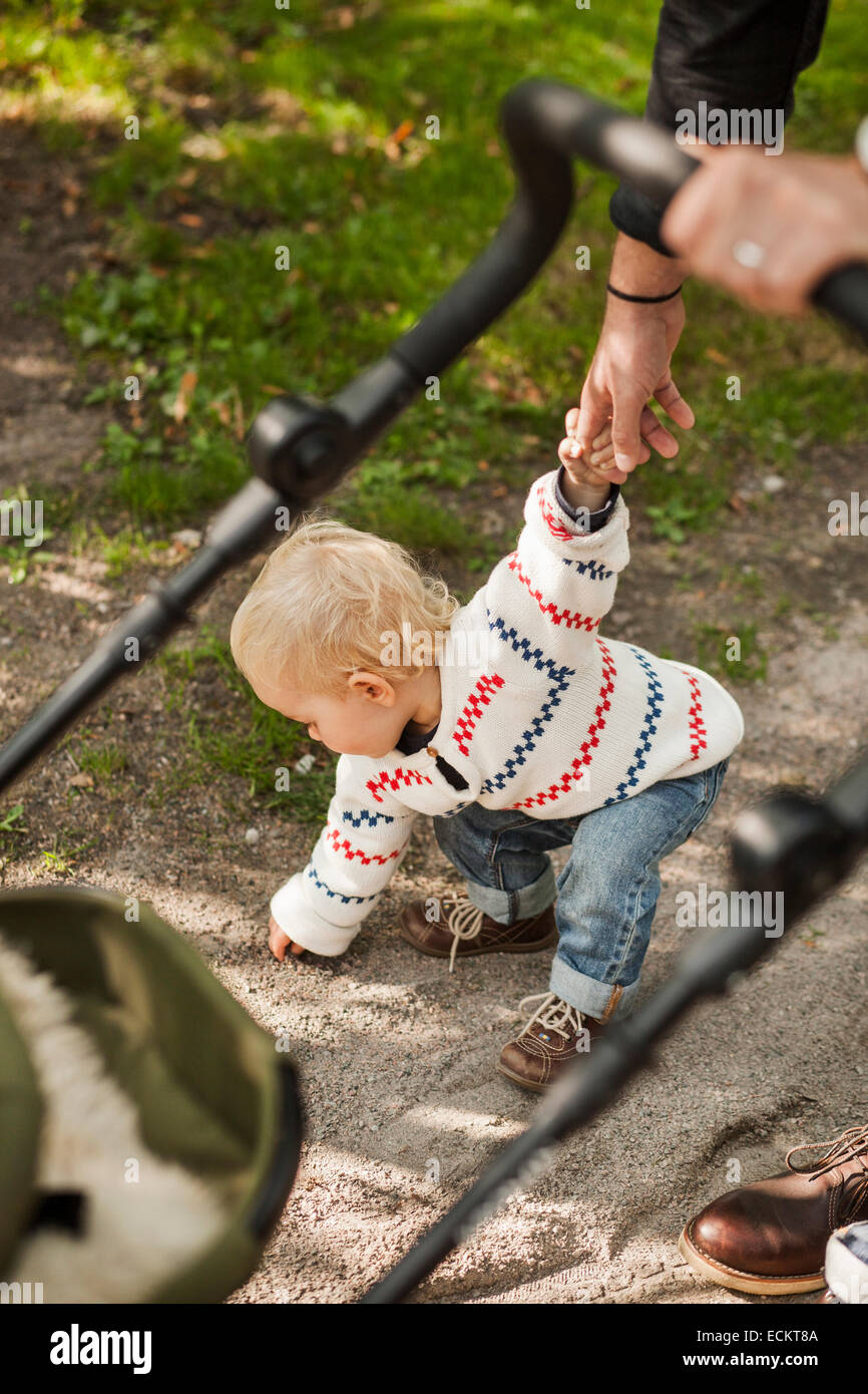 Baby girl picking stone while holding father's hand in park - Stock Image