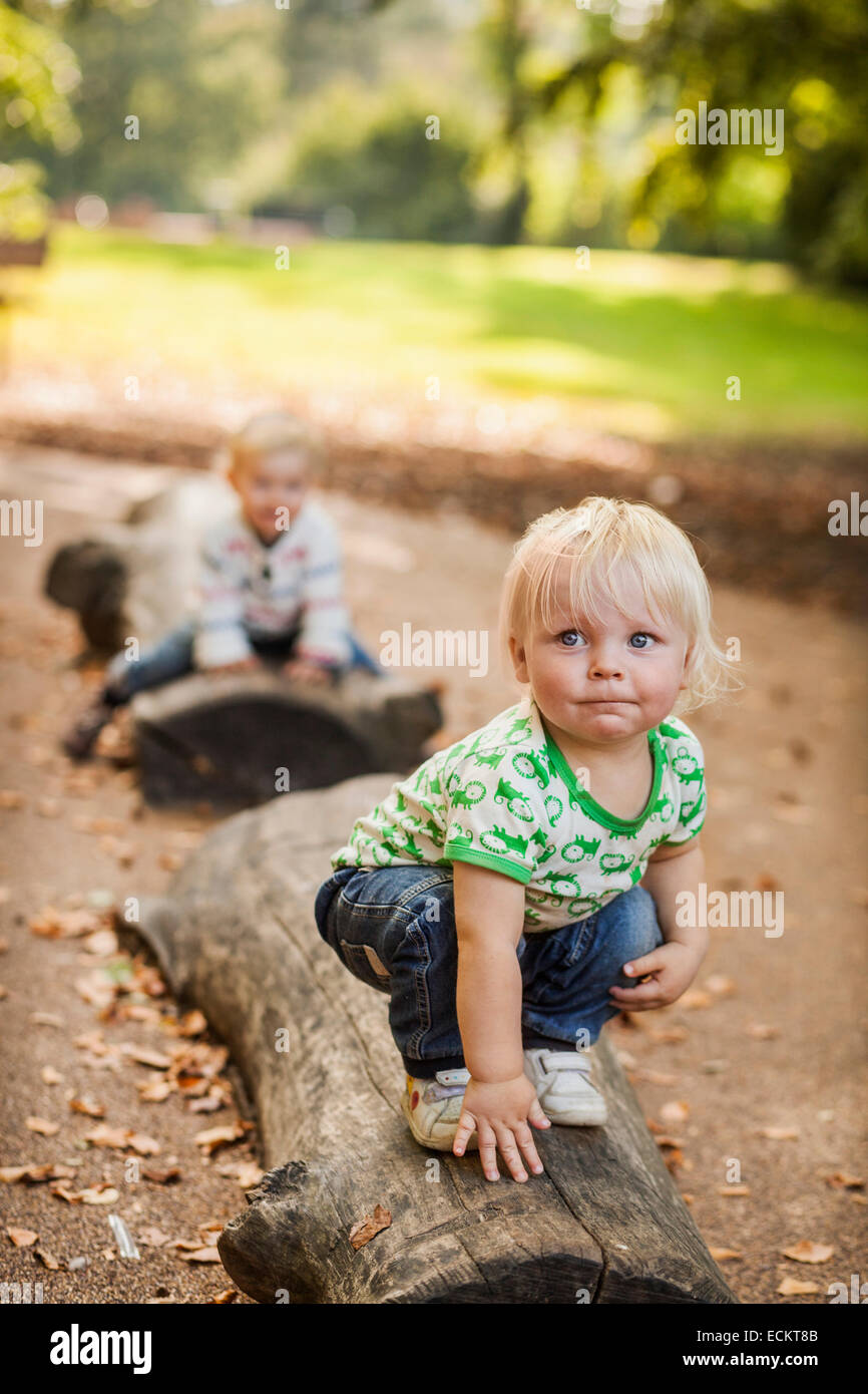 Baby boy looking away while crouching on log at park - Stock Image