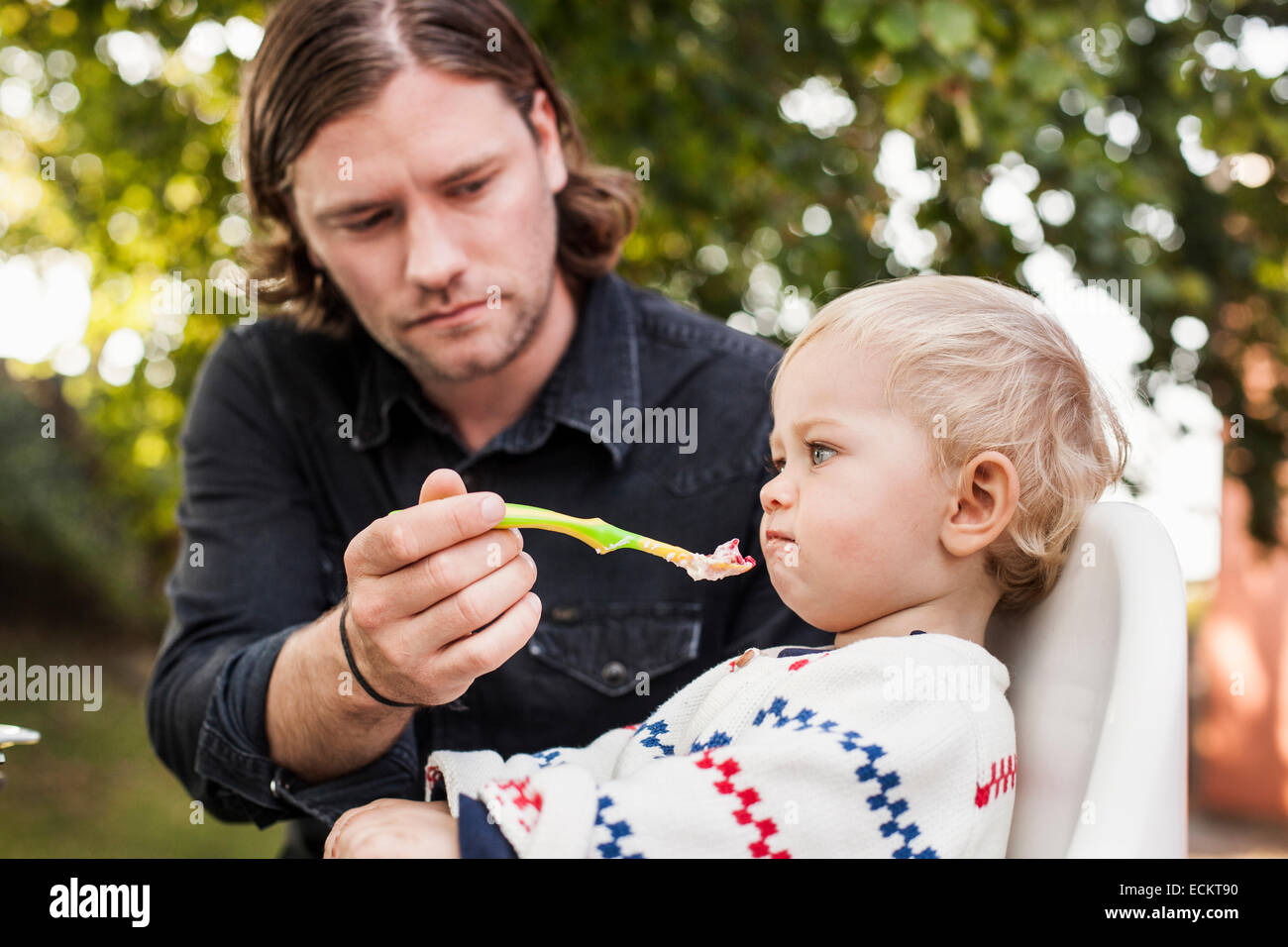 Father feeding angry daughter in park - Stock Image