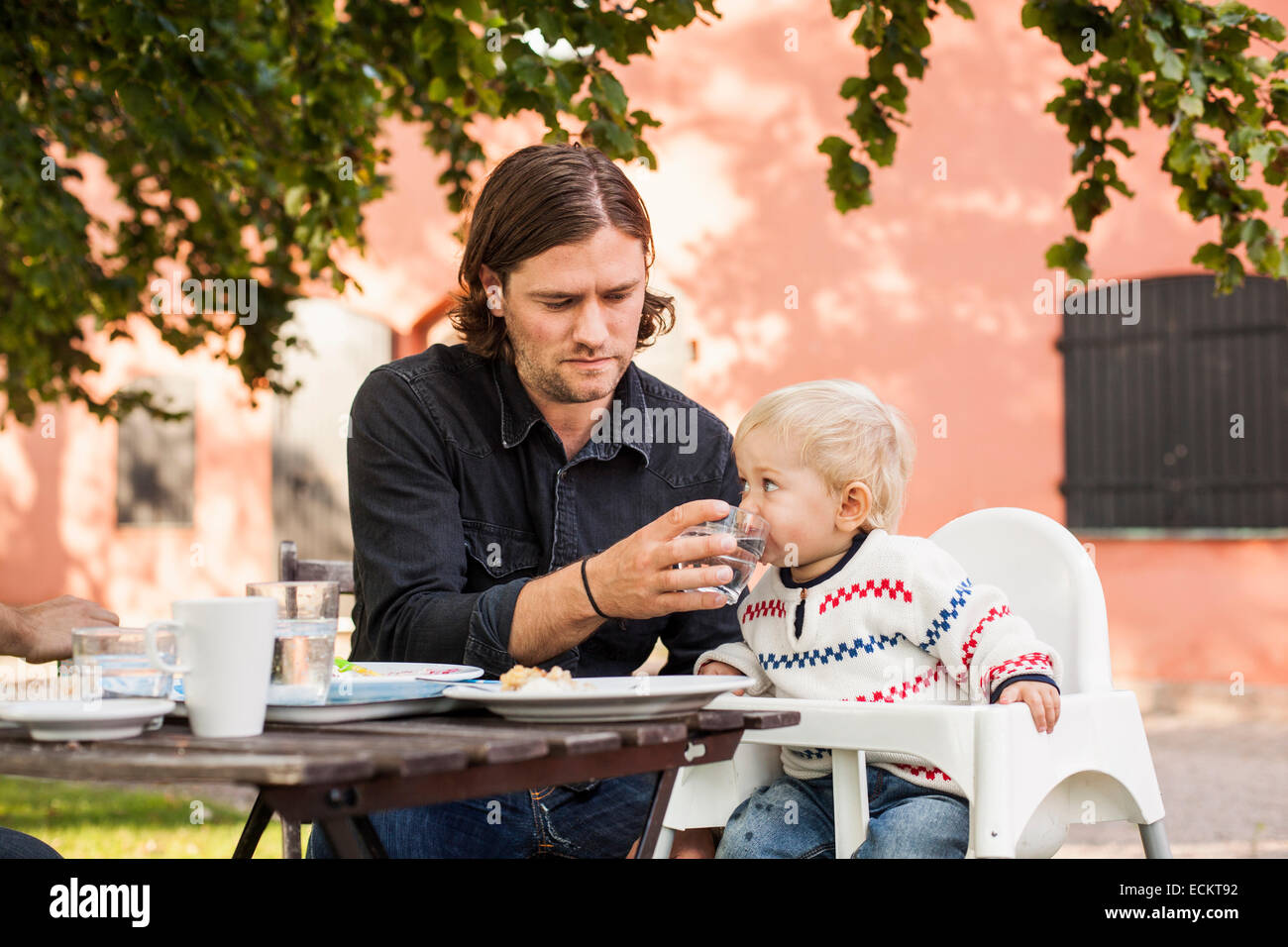 Father feeding water to baby girl in park - Stock Image