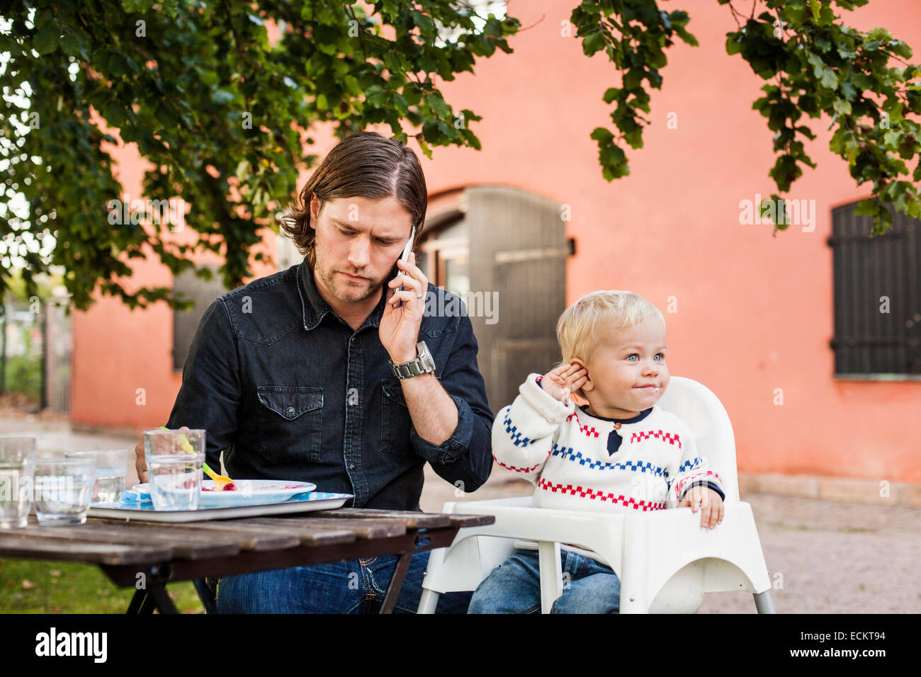 Young man using mobile phone while feeding baby girl in park - Stock Image