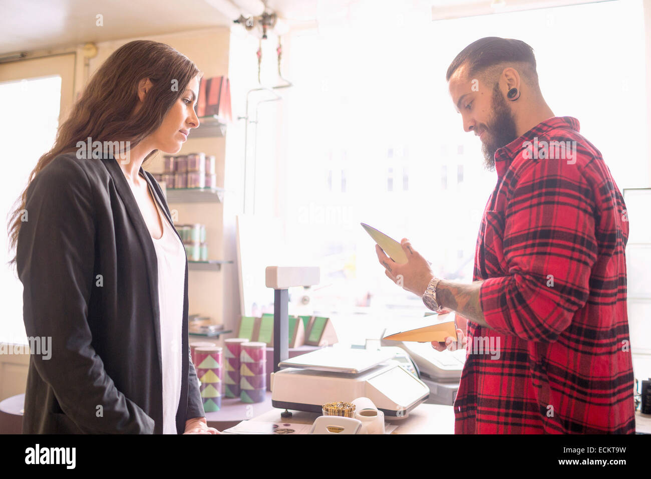 Owner and customer looking at product in candy shop - Stock Image