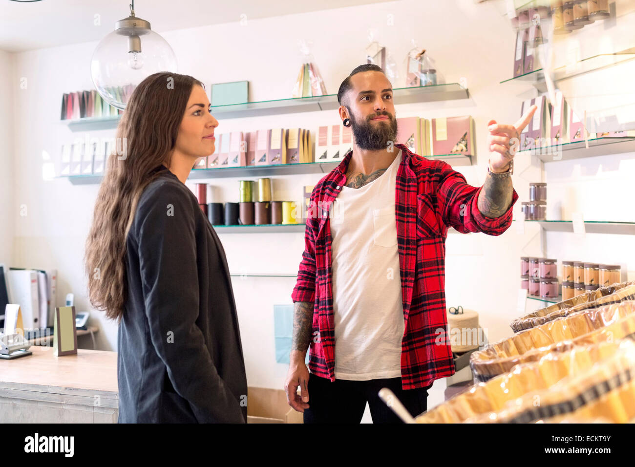 Owner showing products to customer in candy store - Stock Image