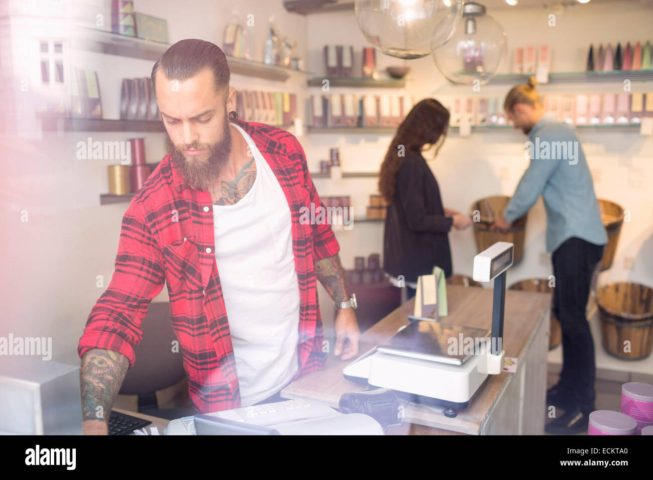 Owner standing at checkout counter while customers shopping in background - Stock Image
