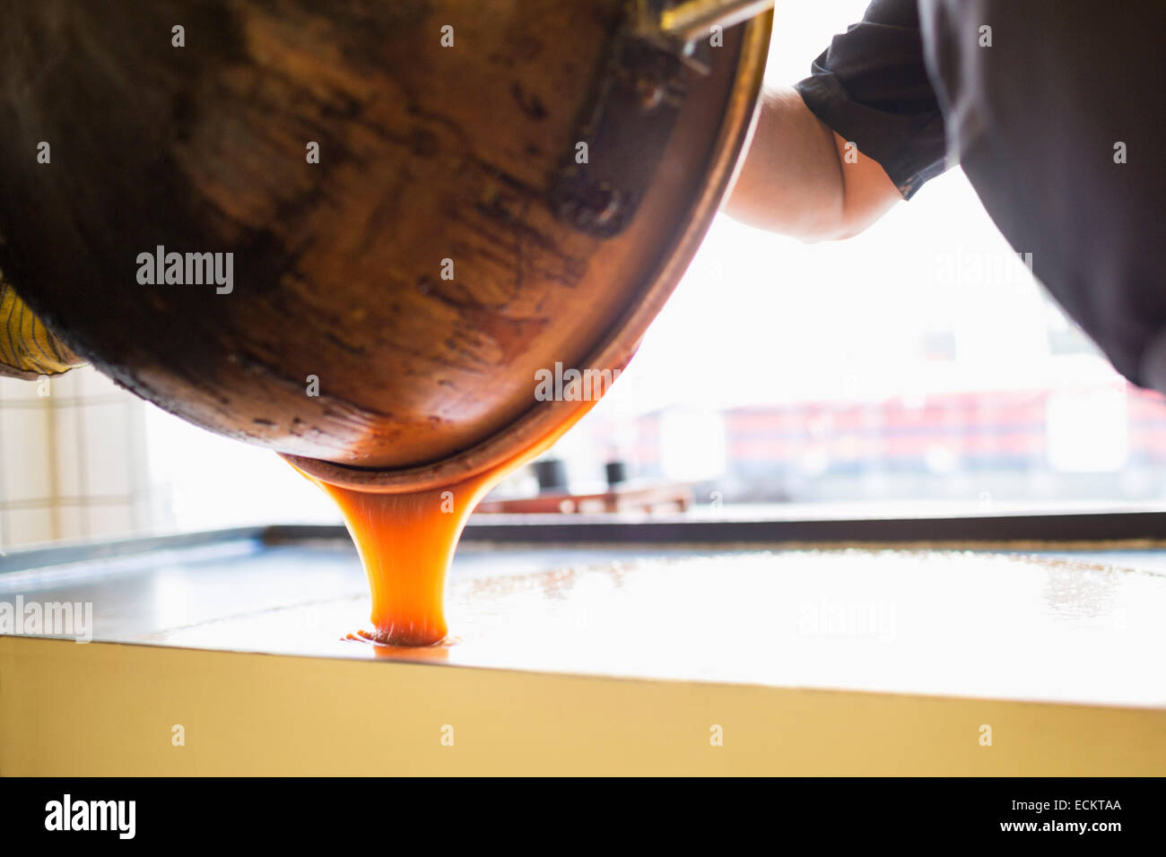 Cropped image of worker pouring caramel in container at candy store - Stock Image