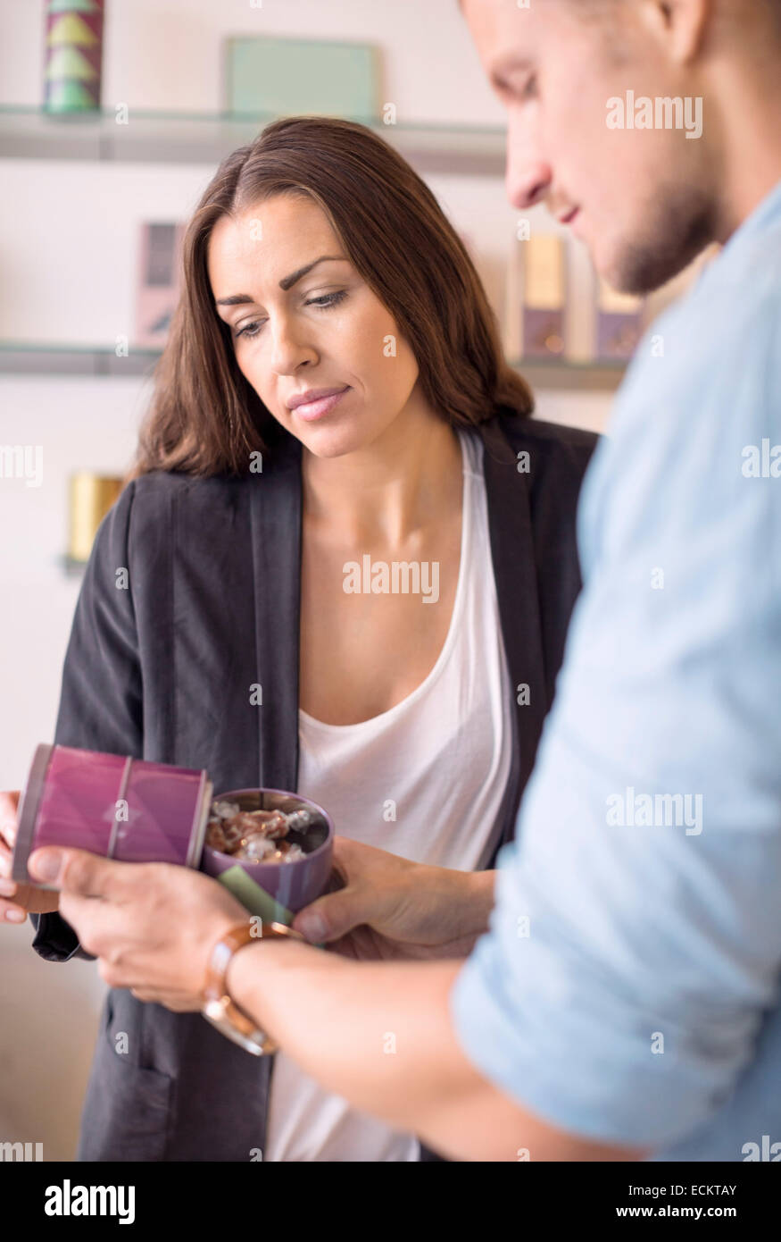 Male worker with colleague verifying product in candy store - Stock Image