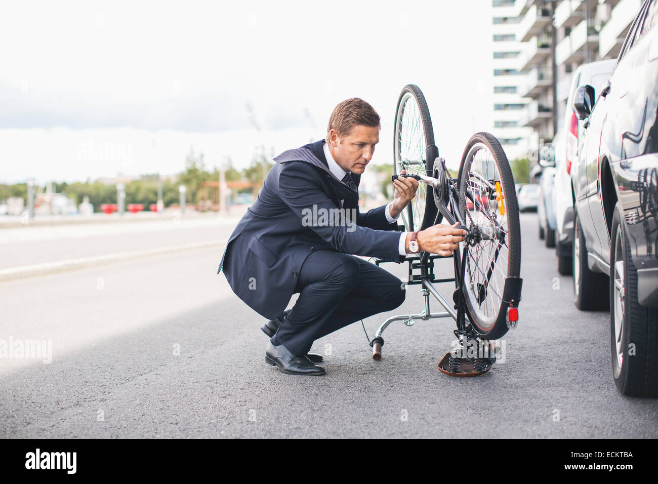 Businessman fixing bicycle chain on city street against sky - Stock Image