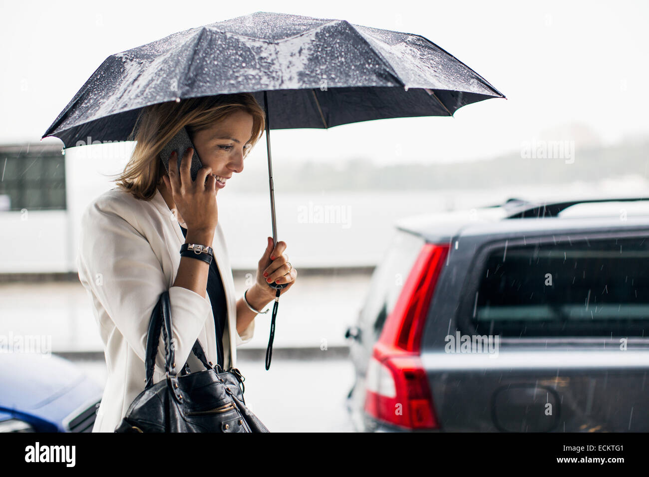 Businesswoman talking on smart phone during rainy season in city - Stock Image